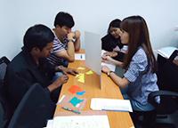 口頭コミュニケーションによるゲーム演習をするスタッフ