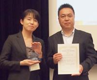 受賞の賞状と盾を持って記念撮影する弊社情報産業研究所 所員